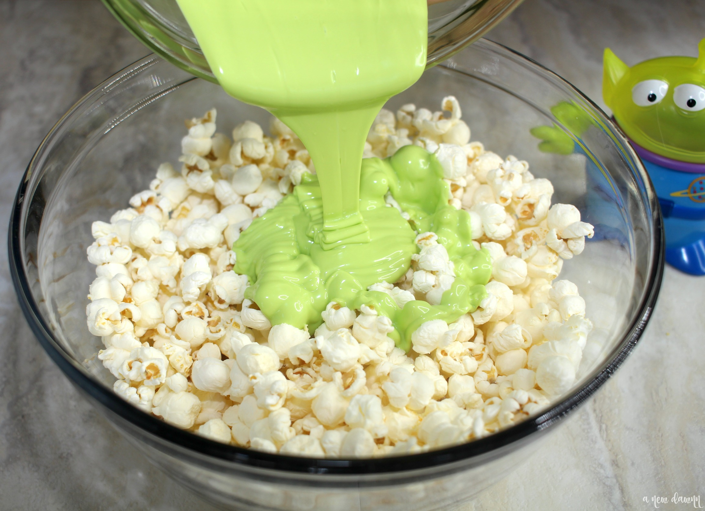 Pouring green melted candy over popcorn