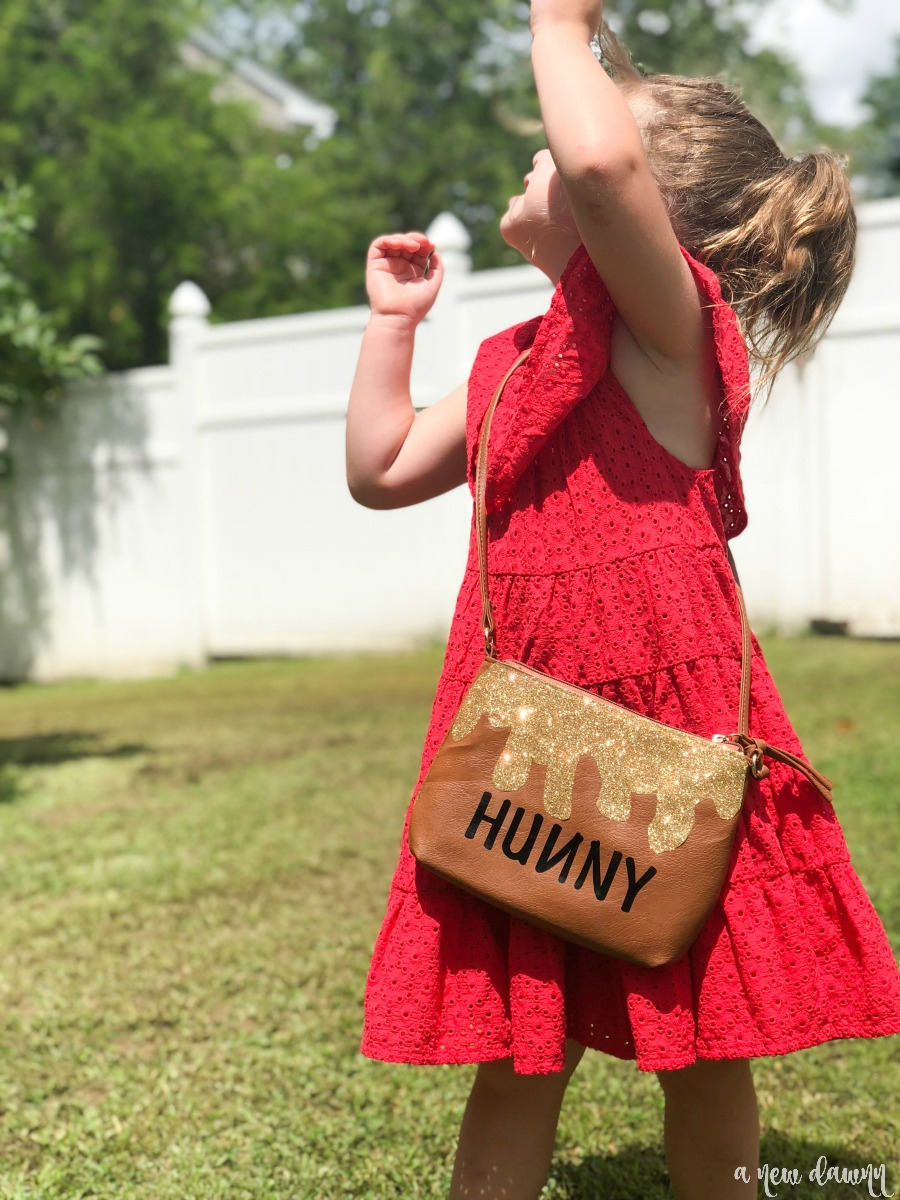 girl in red dress wearing hunny pot purse