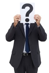 Businessman holding a question mark paper in front of his face