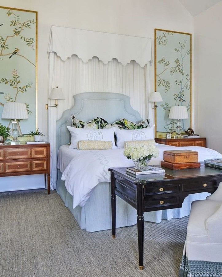 Bedroom with upholstered blue headboard and framed chinoiserie wallpaper panels