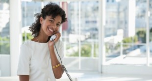 Portrait of a woman talking on a landline phone