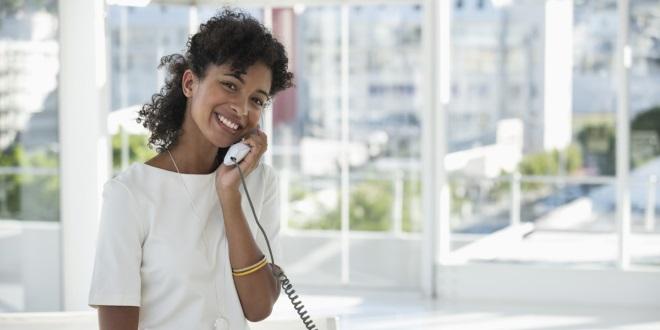 Portrait of a woman talking on a landline phone