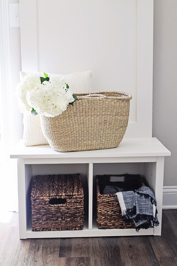 Hall Tree bench seat with wicker basket on top filled with white hydrangea flowers