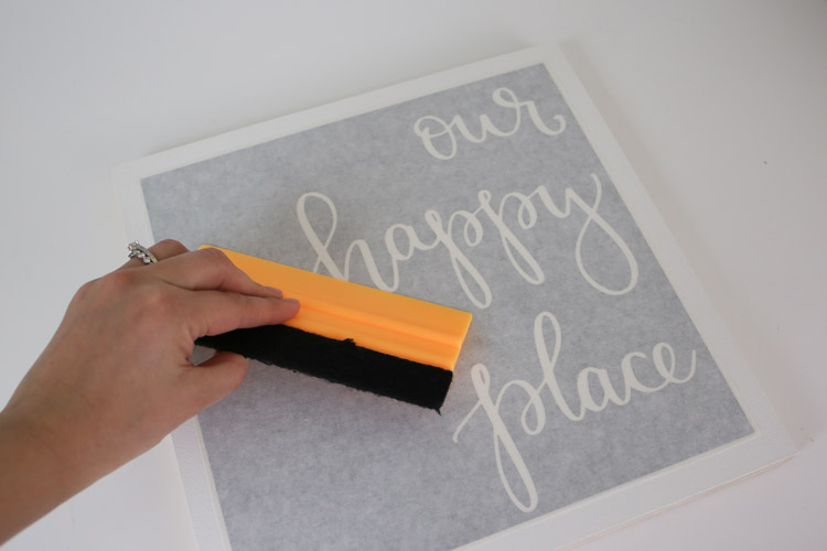 Remove bubbles from transfer tape over vinyl with a squeegee