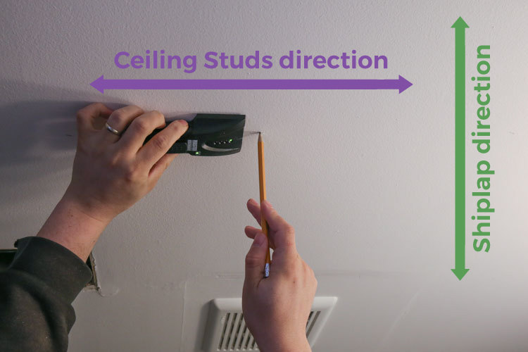 Using a studfinder on the ceiling to locate studs and mark with pencil direction of studs