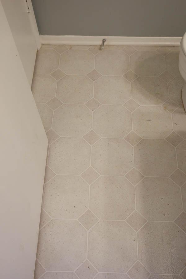 old vinyl tile being replaced in DIY bathroom renovation