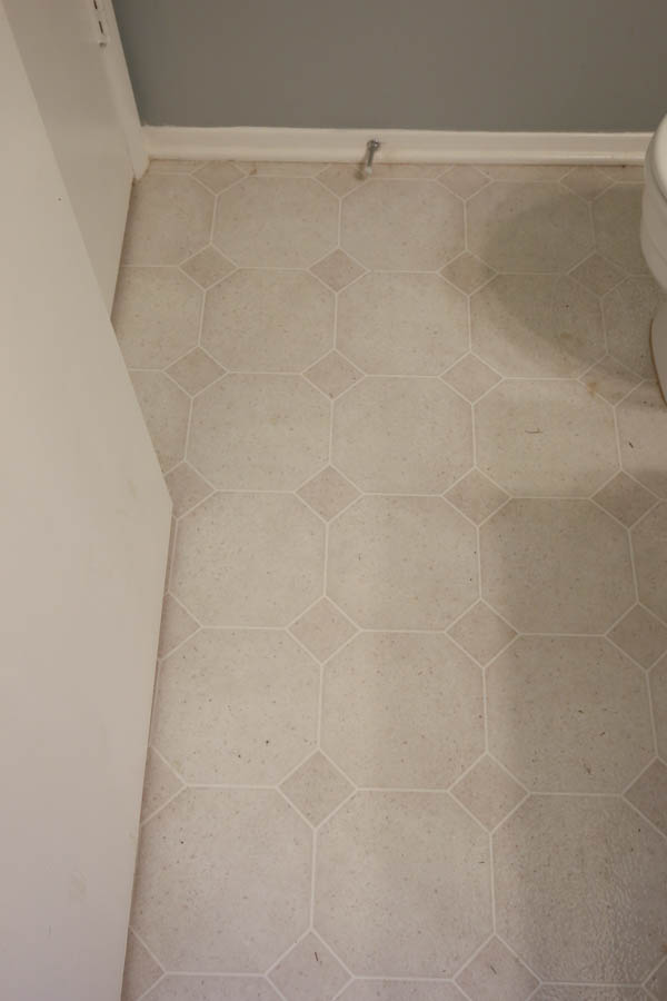 old vinyl tile being replaced in DIY bathroom renovation