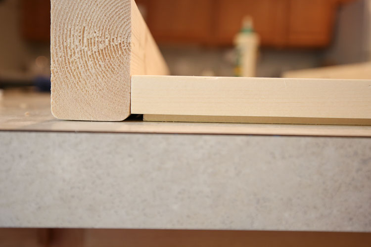 A wood shim under a board to attach vanity legs