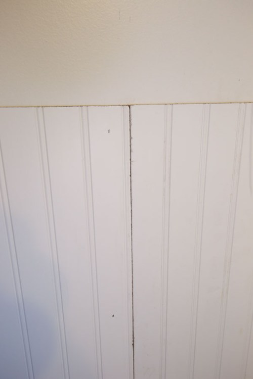 Two beadboard panels being installed on bathroom wall