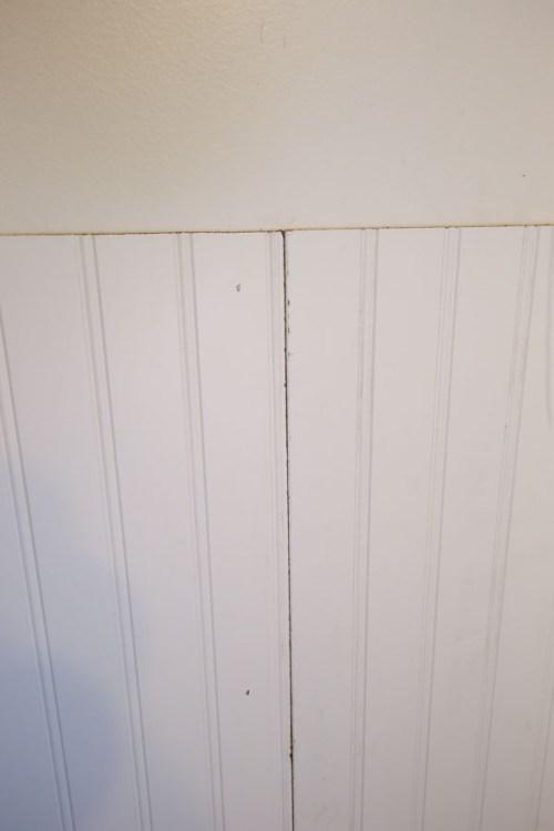 two beadboard panels being installed on bathroom wall - Bead Board Bathroom