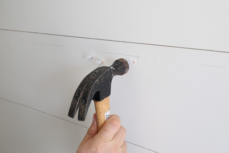 tapping the wall anchors into the holes with a hammer
