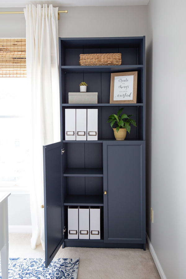 Navy bookcase with styled shelves and DIY magazine holders in a home office