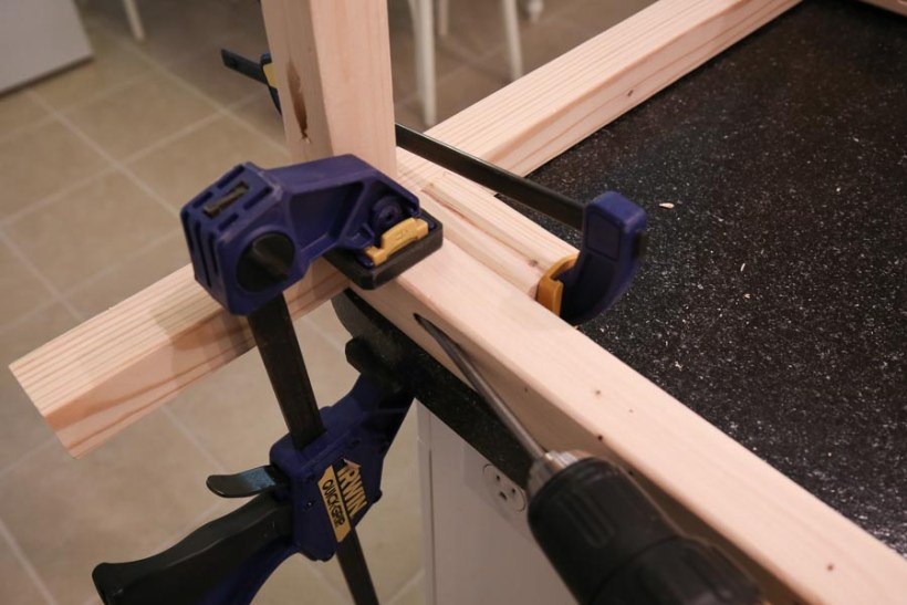 Attaching bottom leg support board brace to vanity leg sides with clamps, pocket holes, and drill
