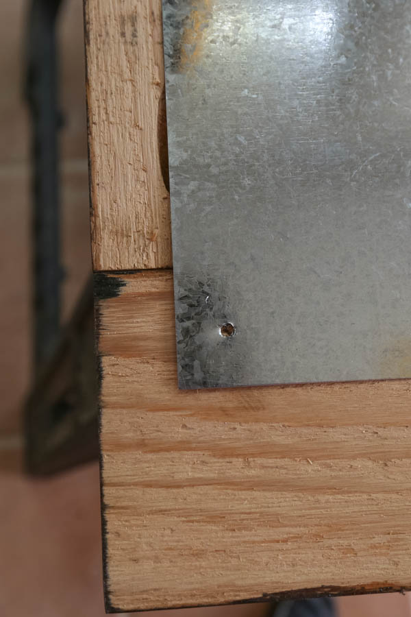Attaching sheet metal to wood frame by first drilling a hole