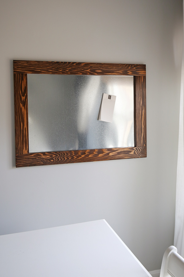 wood framed magnet board hung on office wall with magnetic notepad on it