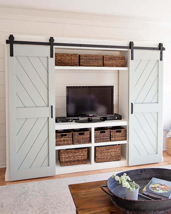 barn door entertainment center DIY with barn doors open showing hidden TV