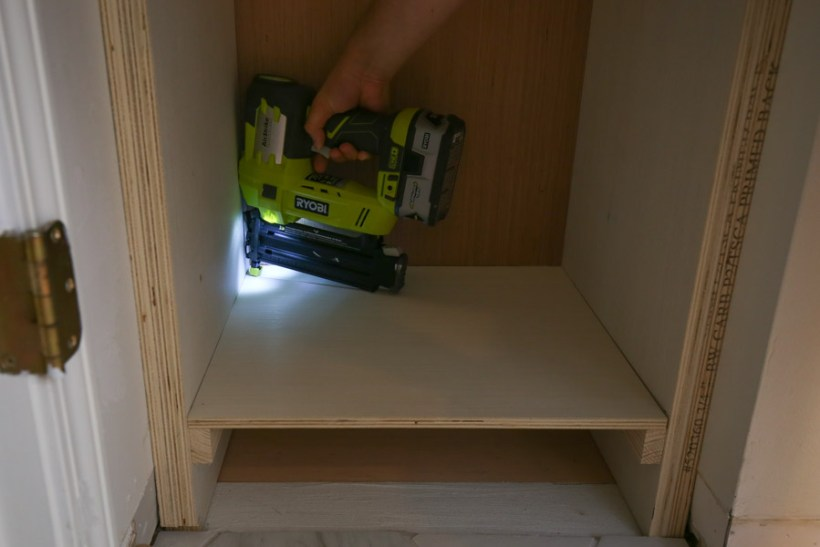 """Attach bottom shelf of DIY built in shelves with brad nails and 1x2 support braces 5 1/2"""" up from the floor"""