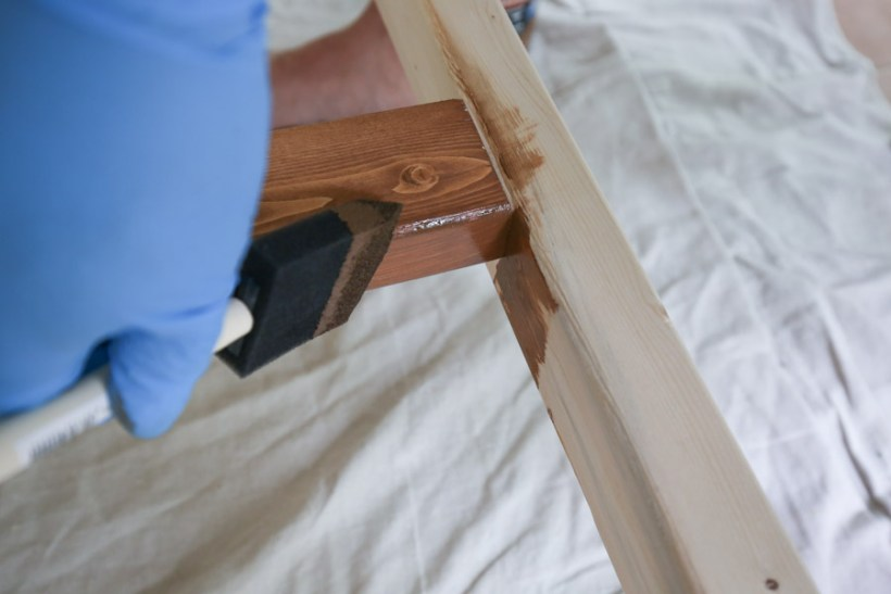 using a foam brush to apply stain to corners of wood project