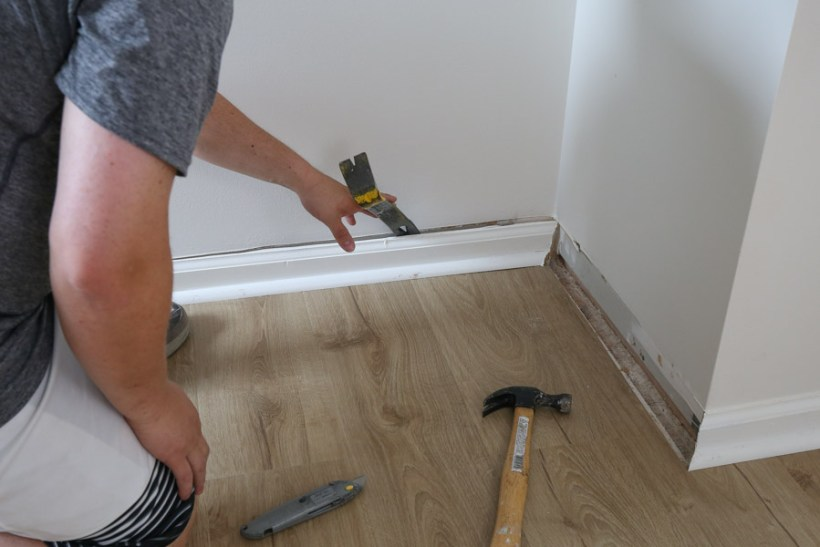 Use a prybar and hammer to remove baseboards from wall after scoring caulk line with utility knife