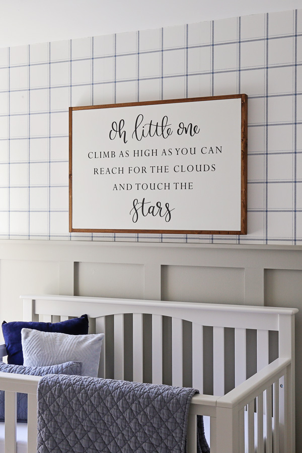 over the crib decor with wood sign over the crib and blue and white wallpaper and gray board and batten