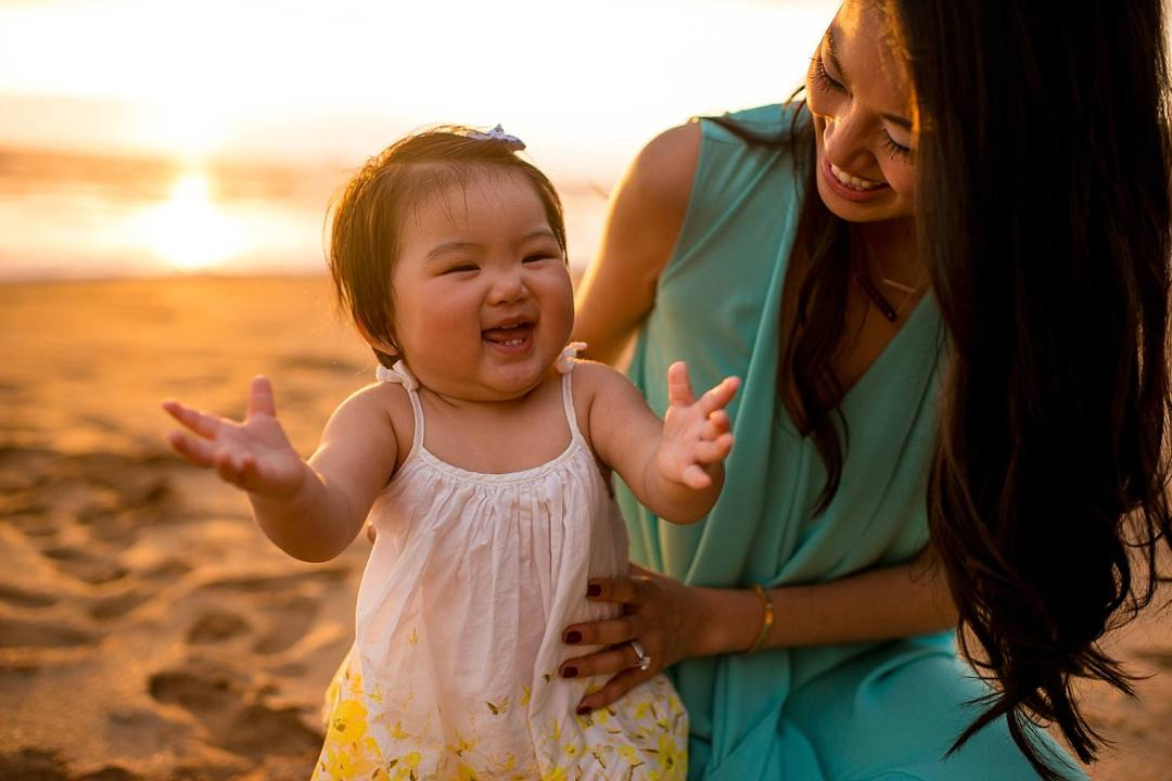 baby clapping with mother on the beach hawaii