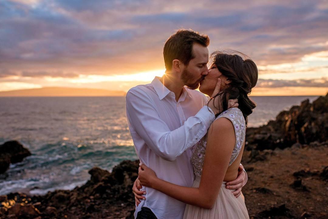 fiances on lava rock in a romantic kiss