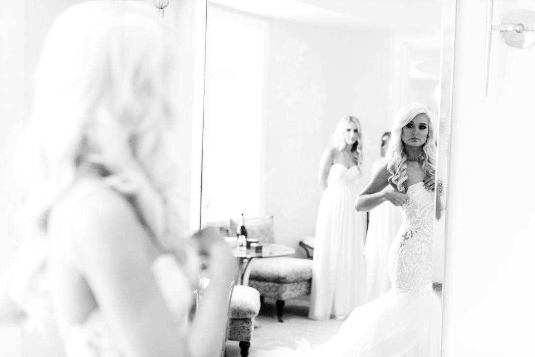 Bride looking in mirror adjusting her Eve of Milady wedding gown