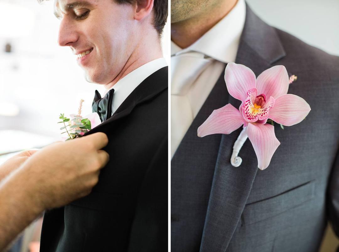 groom getting pink plumeria bouteneer