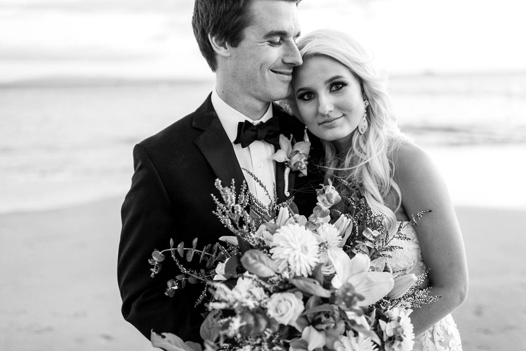 couple cuddling on beach with BEAUTIFUL bride's bouquet from Petals on Maui