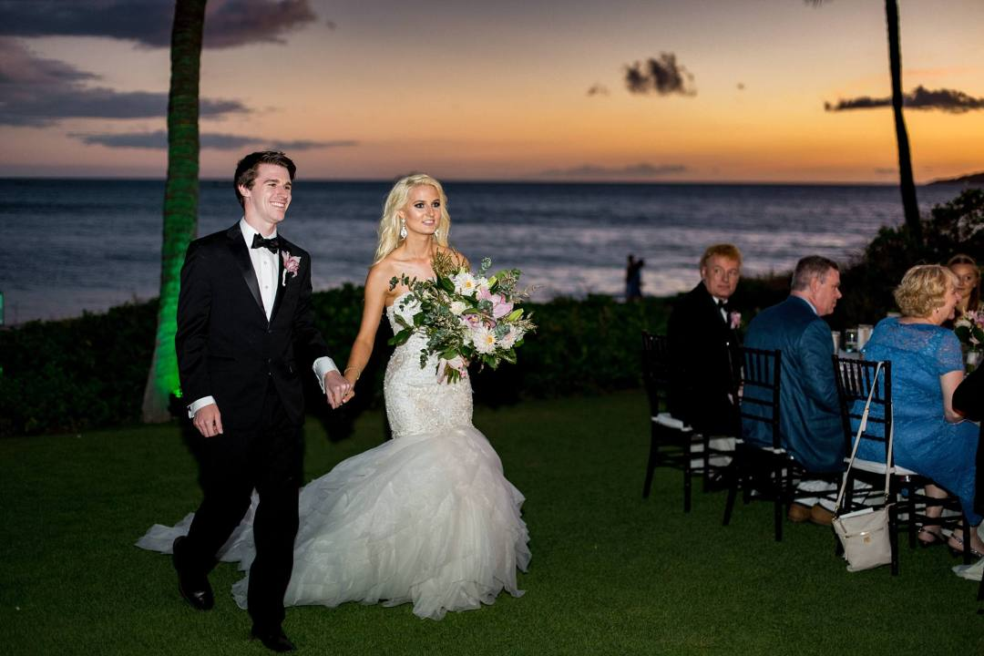 Bride and groom walking into reception at sunset, beautiful grassy area overlooking the water