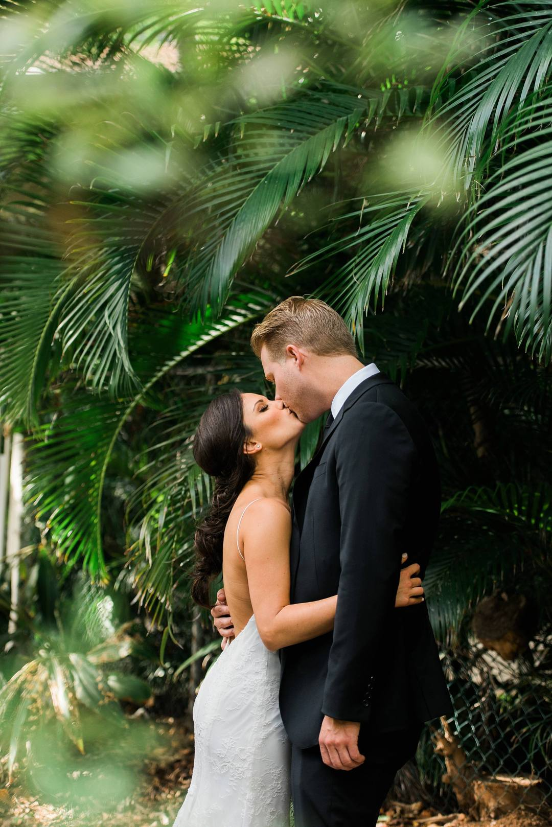 couple kissing by greenery in maui