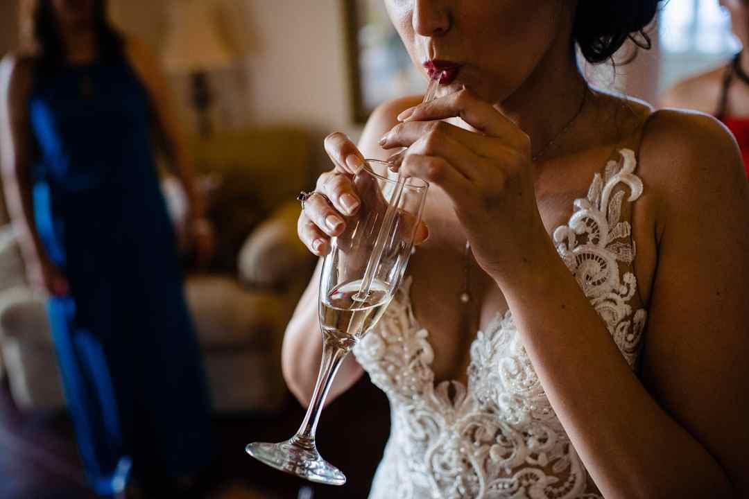bride sipping champagne through a straw