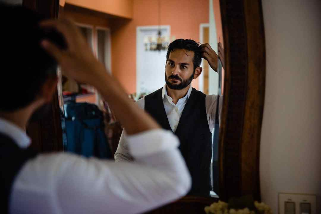 groom fixing his hair before ceremony