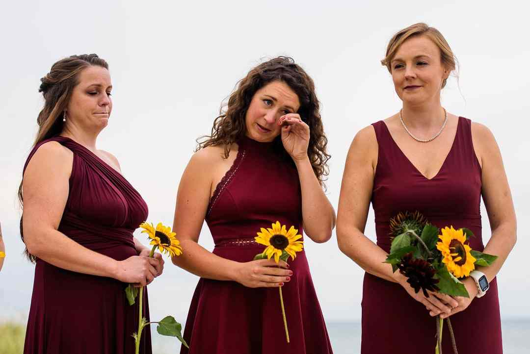bridesmaid wiping tears during wedding