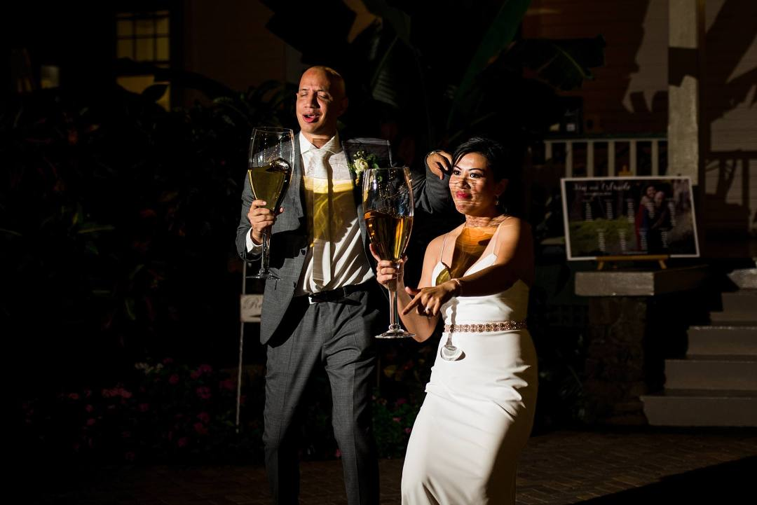 bride and groom with large wine glasses at olowalu plantation house