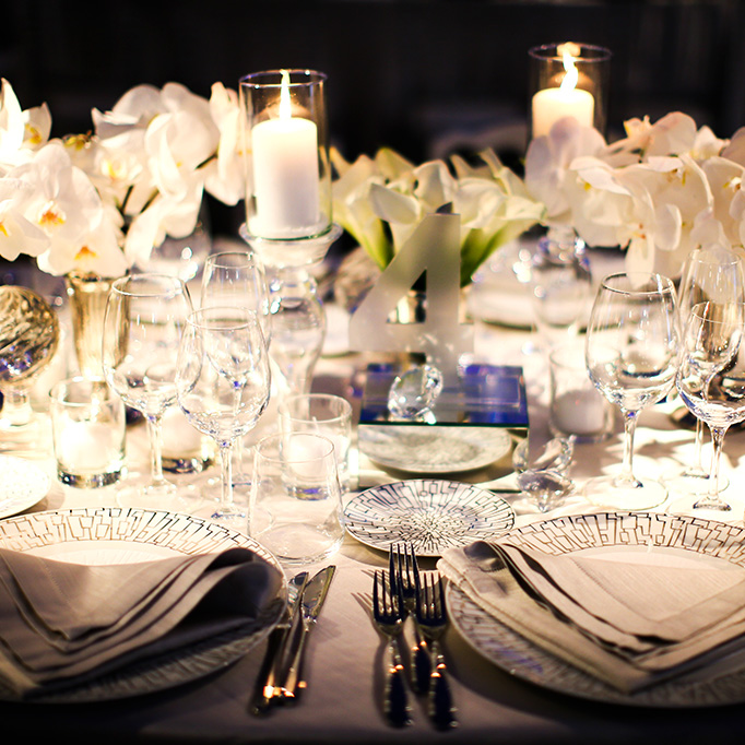 elegant festive dining tables complete with bright bouquet centerpieces in huge colorfully-lit hall