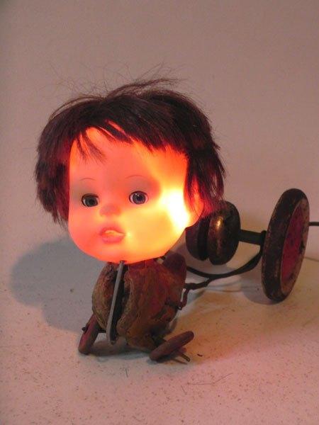 Becui. Sculpture assemblage de vieux jouets. jeu de canard cassé, tête de poupée. Lampe sculpture à roulettes.