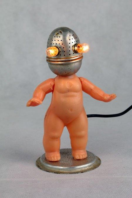 Bethé. Détournement lumineux boule à thé et corps de poupée, sur un filtre de cafetière. Recyclage lumineux, upcycling.