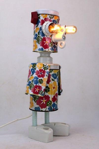 Boileur Personnage assemblage de boites. Sculpture avec 3 boites gigognes en métal fleuries et des composants électriques en porcelaine. Recyclart.