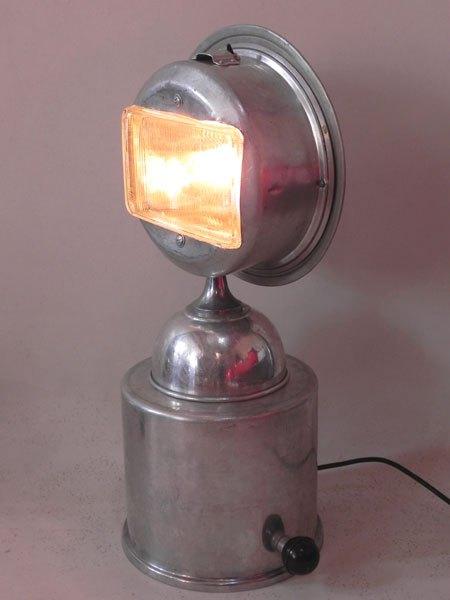 Bucibie. Buste lumineux aluminium et phare. Assemblage de gamelles de camping et un feu avant de voiture.