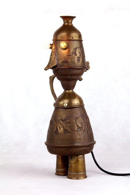 Falorient. Personnage lumineux par assemblage d'objets en laiton. Composé d'une théière, un coquetier et deux mini tasses.
