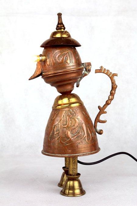 Fatheton. Sculpture personnage lumineux avec un service oriental. Assemblage d'une théière, un couvercle, des éléments de lustre, deux mini verre. Cuivre et laiton.