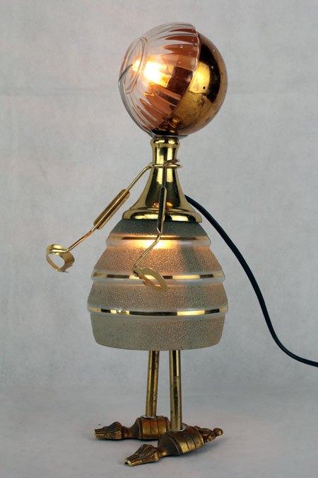 Faveror. Sculpture avec objets anciens. Assemblage d'une verrerie opaline en verre avec rayures dorées, un bol, une coupe de sport dorée...