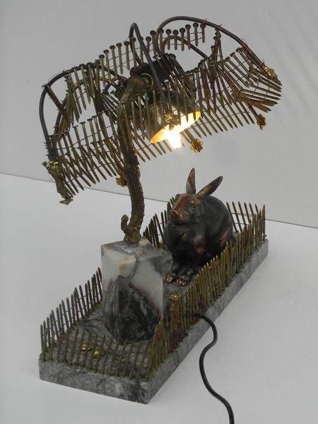 Fernat. Composition lumineuse avec objets bizarres. Assemblage d'un lapin en fonte sur une plaque de marbre, un élément d'applique, recharge clous pour pistolet à clous.