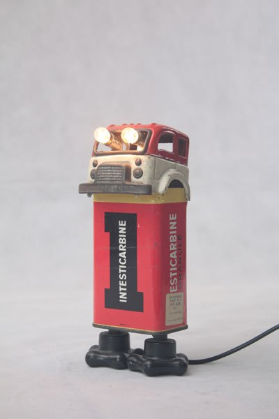 """Goupil02. Personnage lumineux avec un camion et une boite de médicament """"Intesticarbine"""", quincaillerie. métal imprimé, plastique. Rouge. jouet,"""