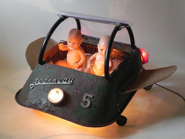 Jeanneau. Véhicule volant sculpture lumineuse. Assemblage d'une brouette trouée et retournée,4 roulettes, optique auto moto, 2 baigneurs....