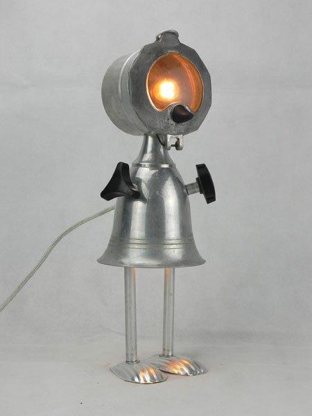 Malunez. Sculpture féminine lumineuse en aluminium. Assemblage d'une cafetière italienne, un filtre, une coupe de sport, boutons, et deux mini moules à madeleine pour les pieds.