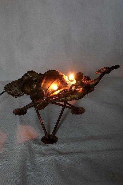 Scarafrique. Scarabée lumineux avec masque africain. détournement d'un masque décoratif d'Afrique en fonte doré sur un porte bougies. Assemblage, animal.