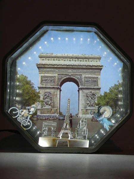Souvenir. Composition dans une boite à gâteaux la Caennaise. boite en métal imprimée Arc de triomphe, personnage en plomb, fanfare, cycliste et monuments parisiens en plastique.
