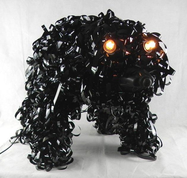 VHSB. Sculpture chien bande magnétique. Assemblage de bande VHS sur des emballages plastiques.
